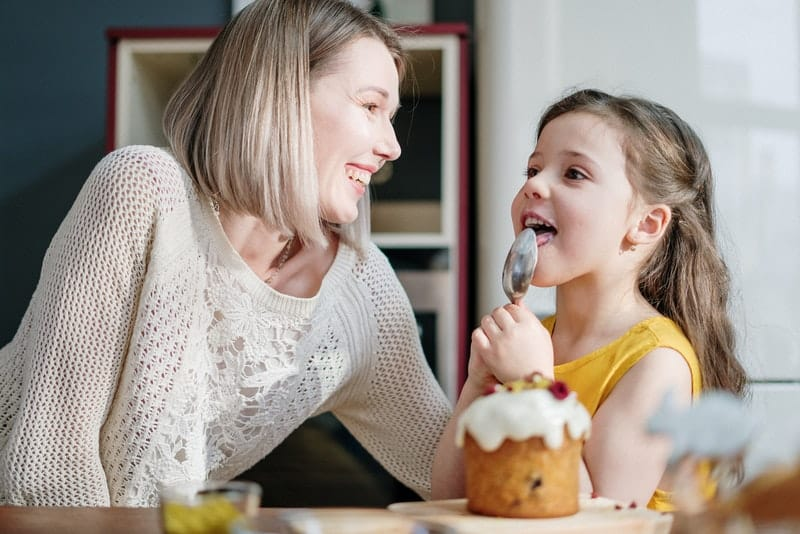 Eine lächelnde Frau sieht zu, wie ihre Tochter Muffins isst