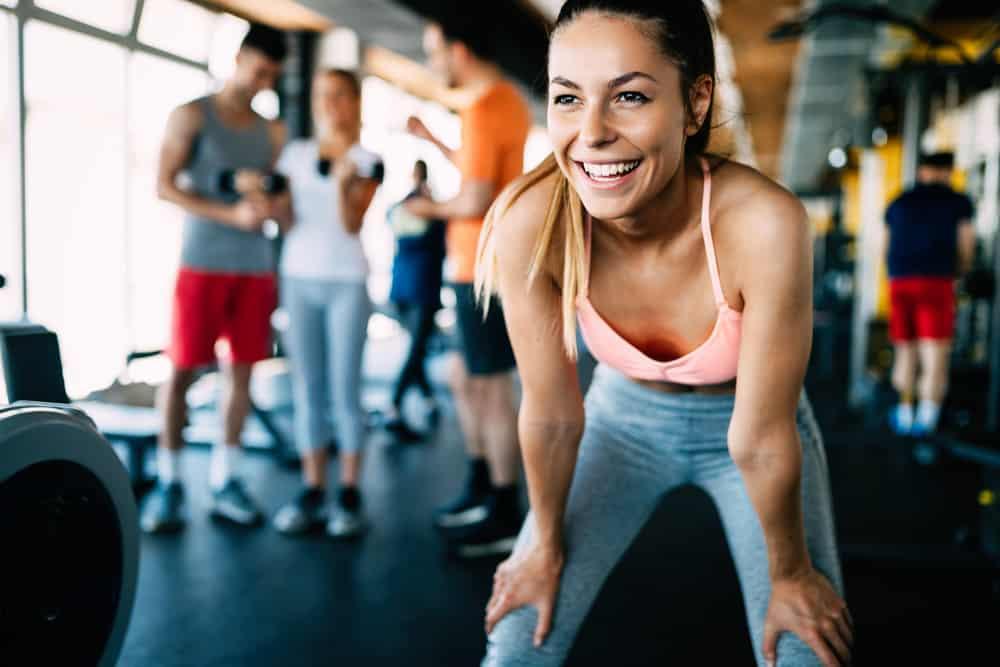 Eine schöne lächelnde Frau im Fitnessstudio steht nackt