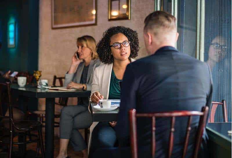 Eine schwarze Frau mit Brille und ein Mann im Anzug sitzen und reden in einem Café