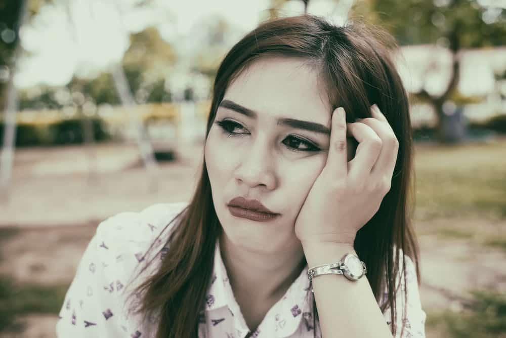 Eine traurige asiatische Frau sitzt draußen