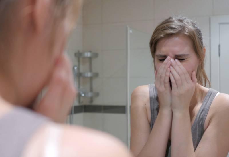 Frau, die im Badezimmer weint