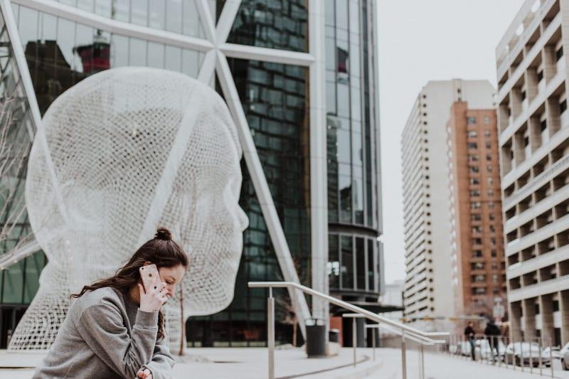 Frau sitzt auf dem Boden, der Smartphone nahe Gebäude hält