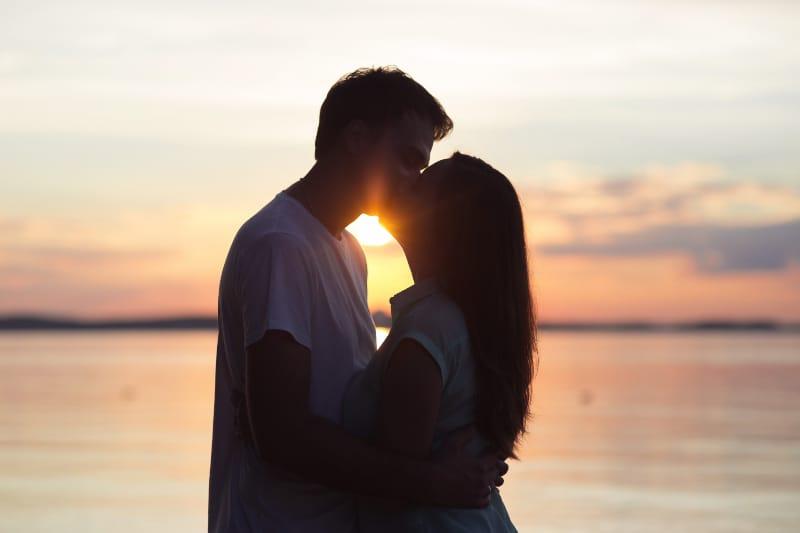 Liebespaar, das bei Sonnenuntergang küsst