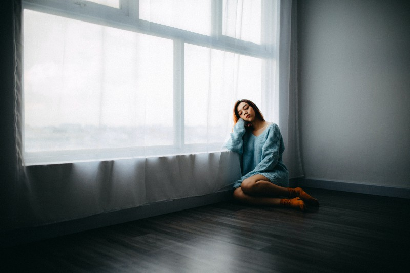Mädchen sitzt auf dem Boden in der Nähe von Fenster