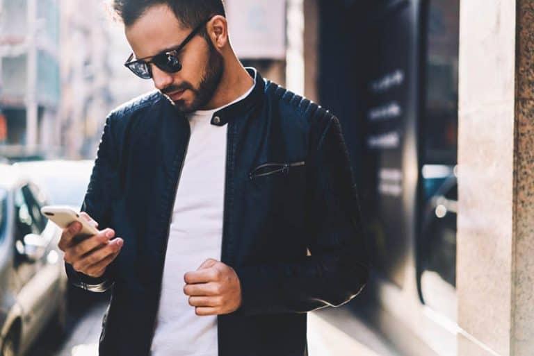 Mann, der Telefon beim Gehen benutzt