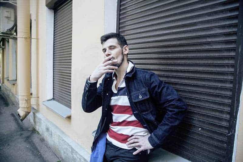 Mann raucht draußen Zigarette