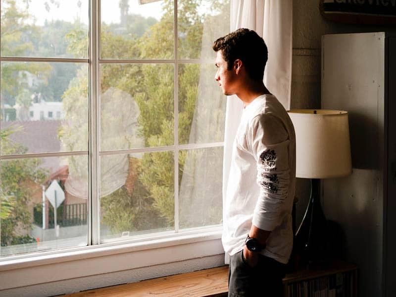 Mann sieht nachdenklich aus, während er durch das Fenster schaut