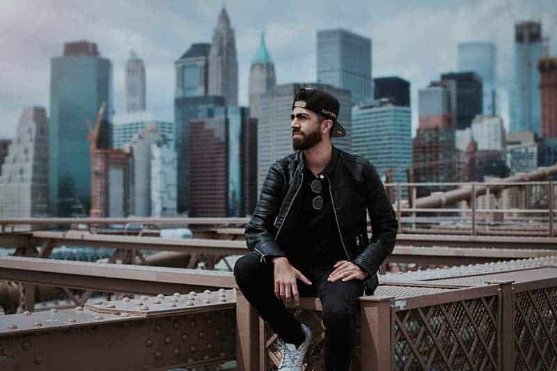 Mann trägt schwarzen Hut und sitzt oben auf der Brücke
