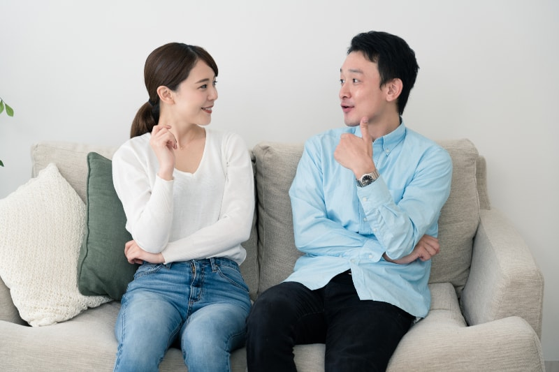 Mann und Frau unterhalten sich auf dem Sofa