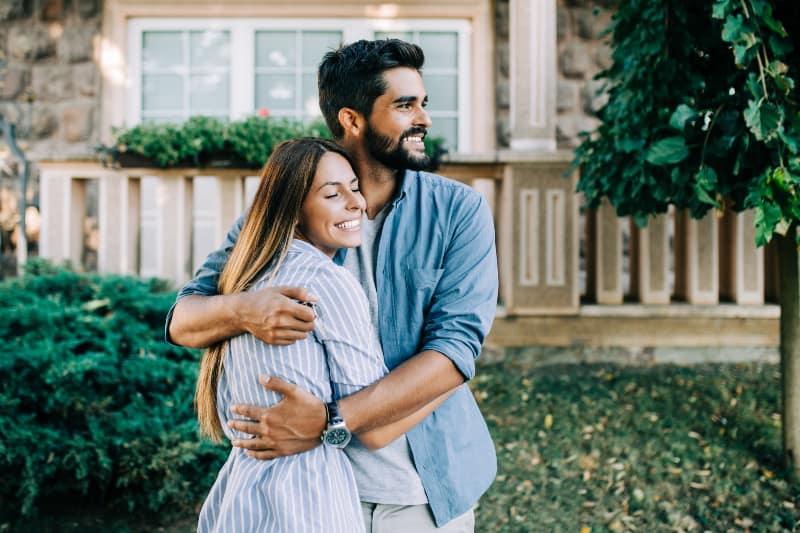 Paar umarmt sich vor dem Haus