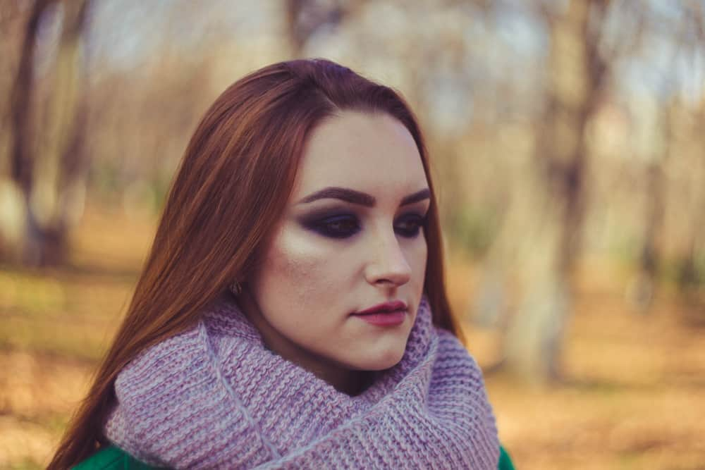 Porträt eines rothaarigen Mädchens mit einem Schal im Park