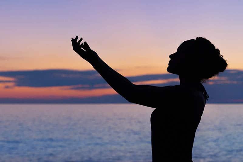 Silhouette der Frau, die ihre Hand hebt