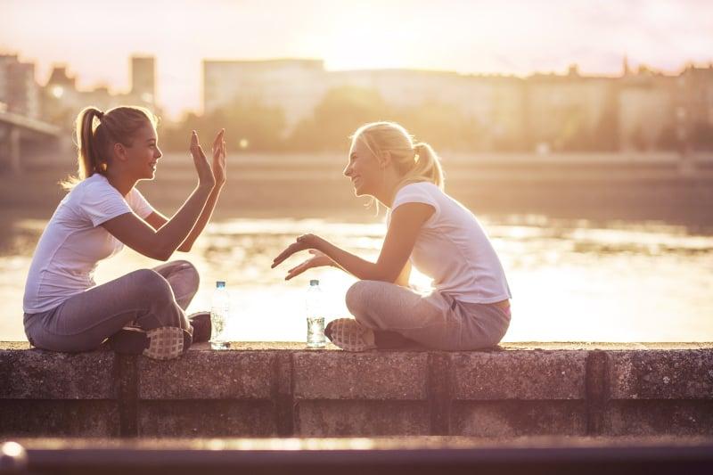 Zwei junge Frauen sitzen nach dem Laufen an der Wand