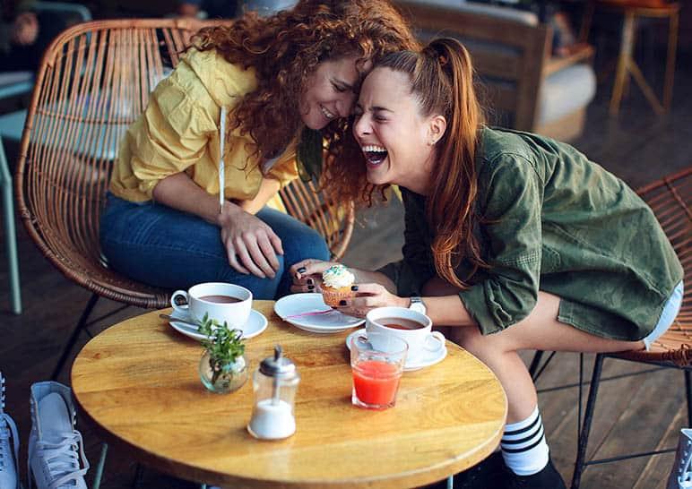 Zwei lächelnde Mädchen sitzen und trinken Kaffee