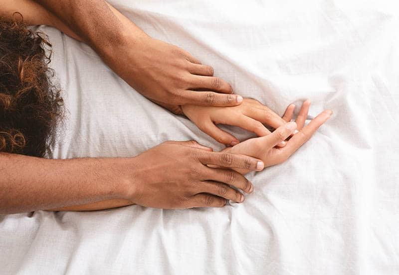 die ineinander verschlungenen Arme eines Mannes und einer Frau auf dem Bett