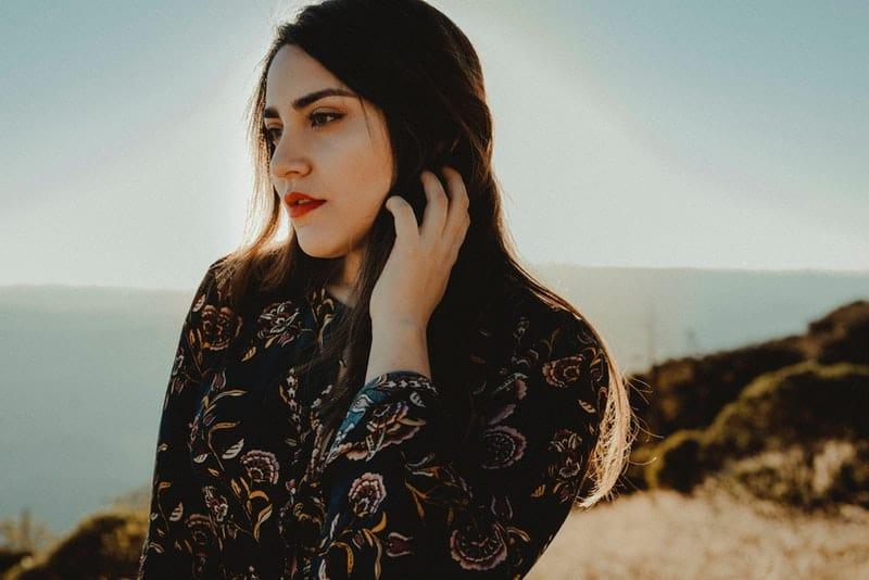 ein Porträt einer Frau, die auf einem Hügel über dem Meer steht