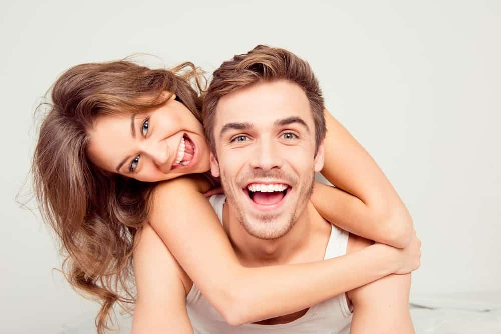 ein lächelnder Mann und eine lächelnde Frau in einer Umarmung