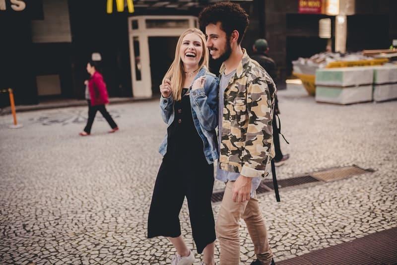 ein lächelndes Liebespaar, das den Gang entlang geht
