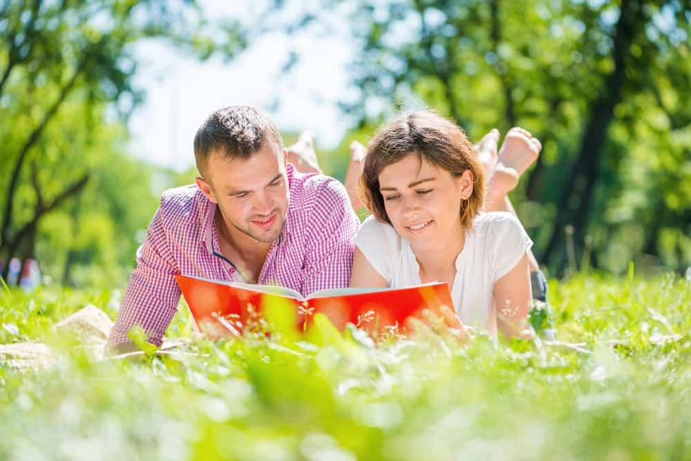ein lächelndes Barfußpaar, das im Gras liegt und ein Buch liest