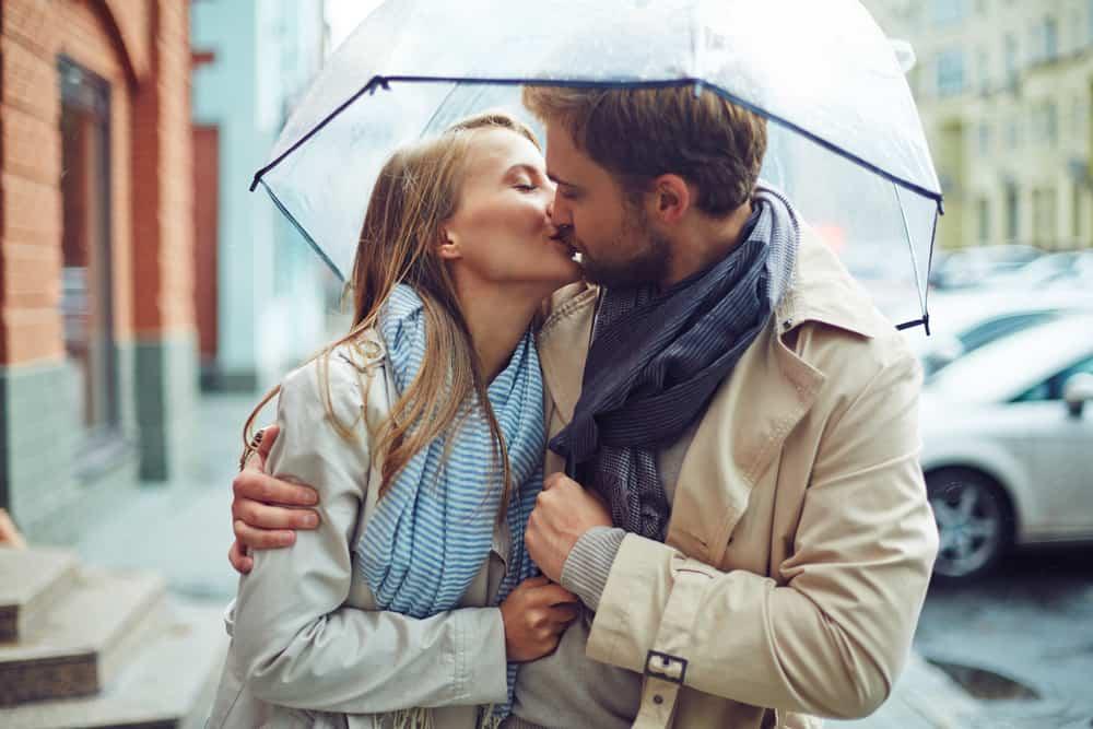 ein liebendes Paar, das sich im Regen küsst