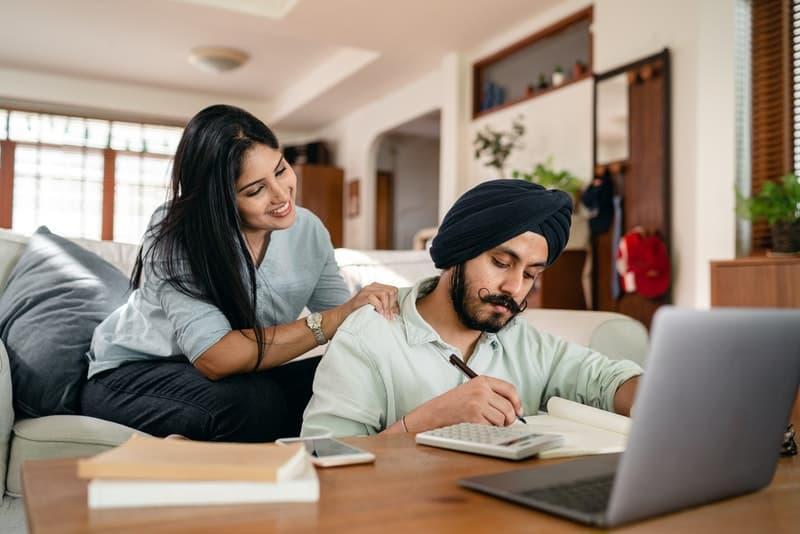 eine lächelnde Frau, die einen Mann massiert, der etwas auf einem Laptop tut