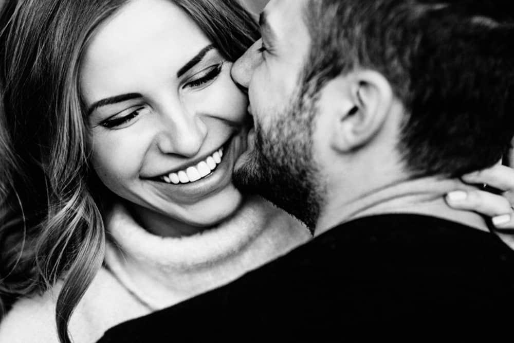 eine lächelnde Frau in den Armen eines Mannes mit Bart