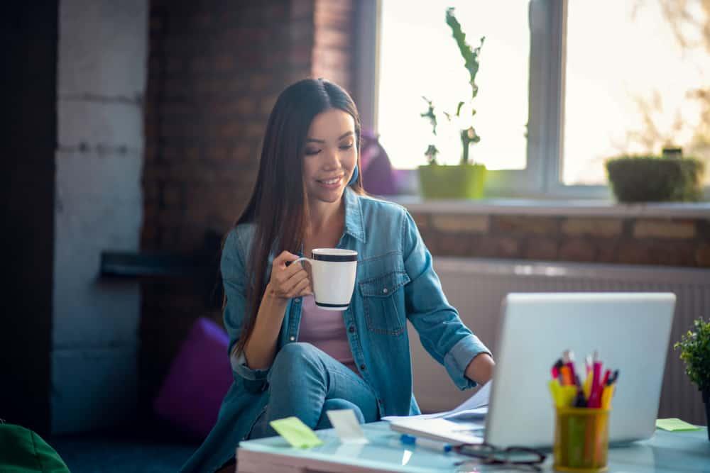 eine lächelnde Frau mit einem heißen Trank, der an einem Laptop arbeitet