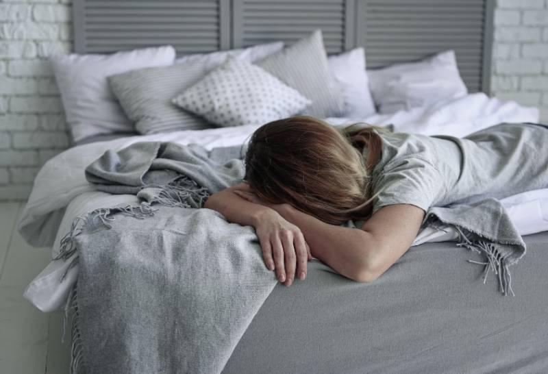 müde Frau auf dem Bett liegen