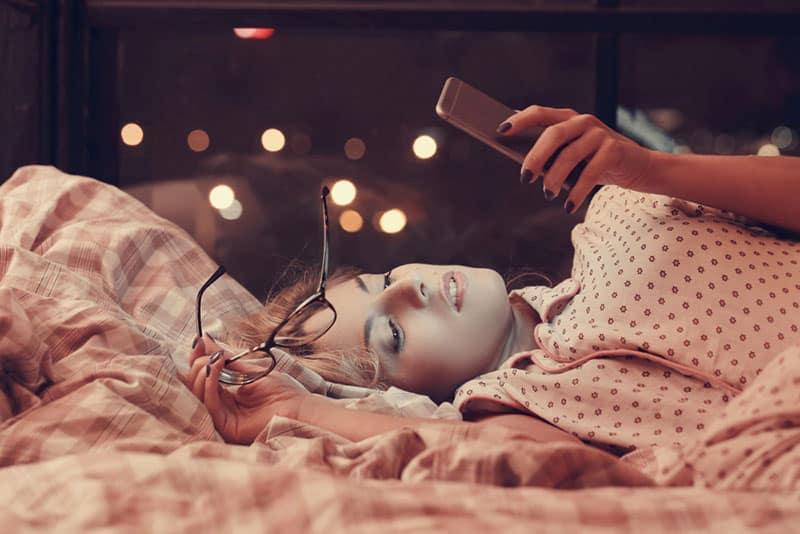 schöne junge Frau, die auf Bett liegt und auf ihr Telefon schaut