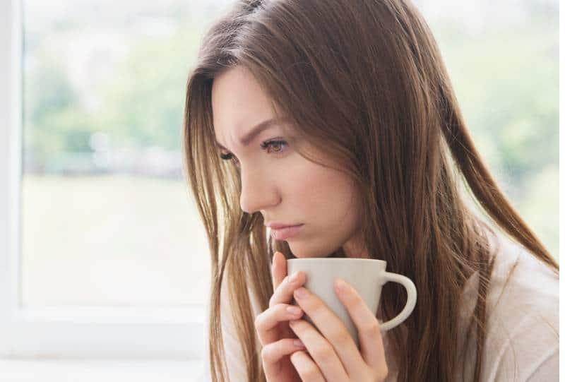 traurige Frau, die Tasse hält und zu Hause denkt