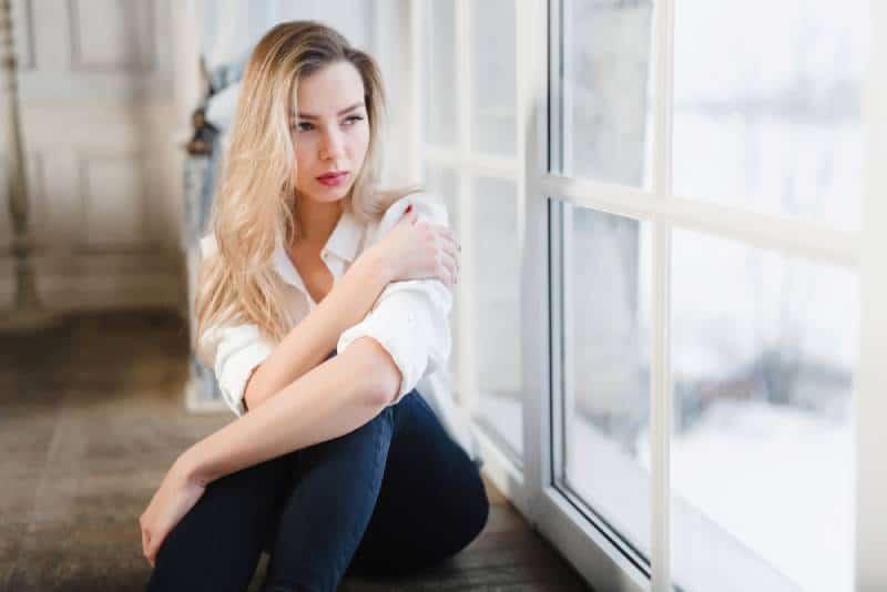 traurige Frau, die auf Parkettboden durch Fenster sitzt