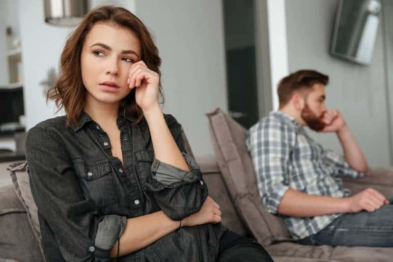 trauriges Paar, das drinnen am Sofa sitzt