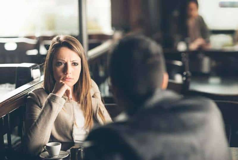 verärgerte Frau, die Mann im Café ansieht