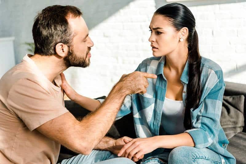 verrückter Mann, der Finger auf Frau zeigt