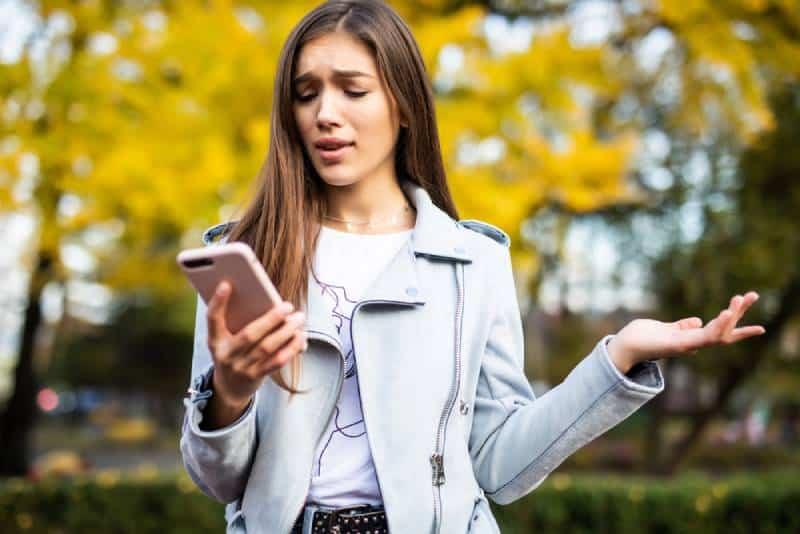 verwirrte Dame, die ihr Telefon im Stadtpark betrachtet