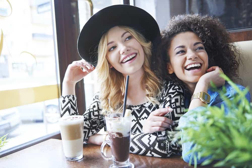 zwei lächelnde Frauen, die in einem Café sitzen