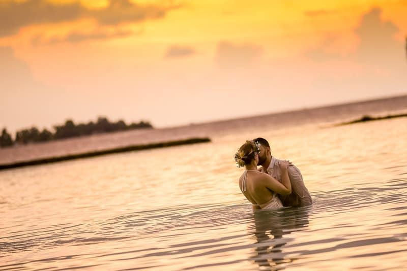 Das Brautpaar steht im Wasser und küsst sich