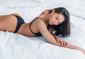 Auf dem Bett liegt eine hübsche Brünette in Dessous