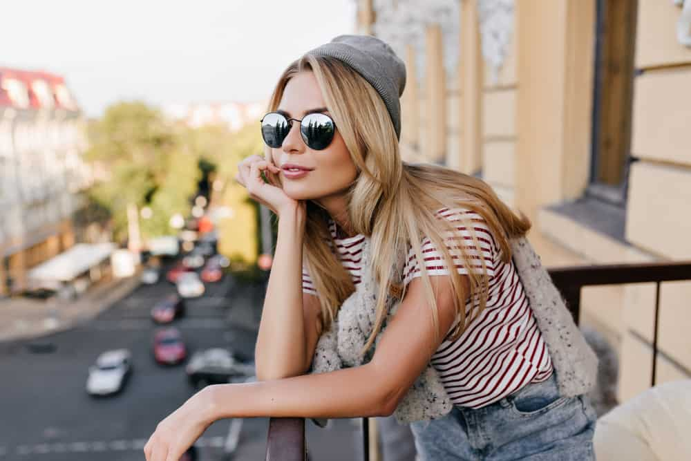 Auf dem Balkon steht eine Blondine mit Brille