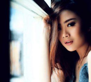 Am Fenster ist ein sehr attraktives Mädchen abgebildet