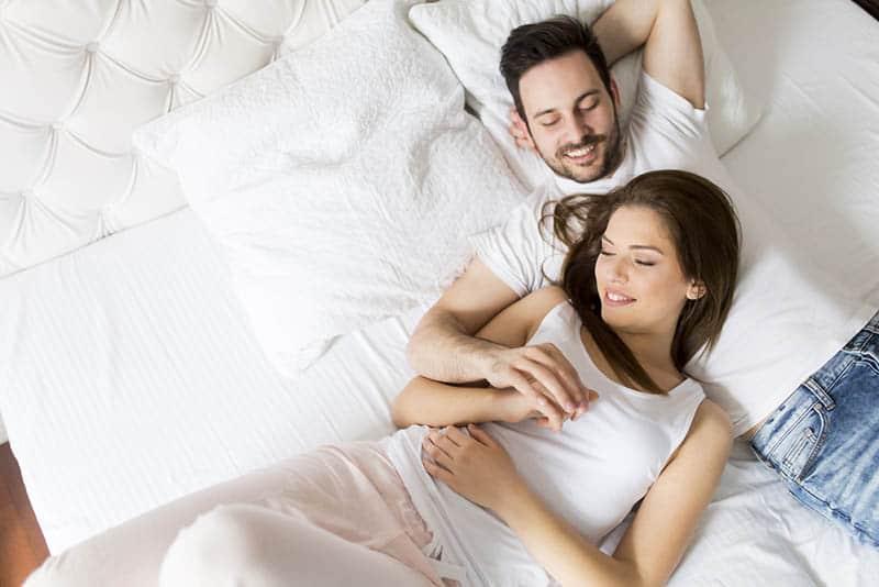 Der glückliche Mann und die glückliche Frau liegen im Bett und halten sich an den Händen