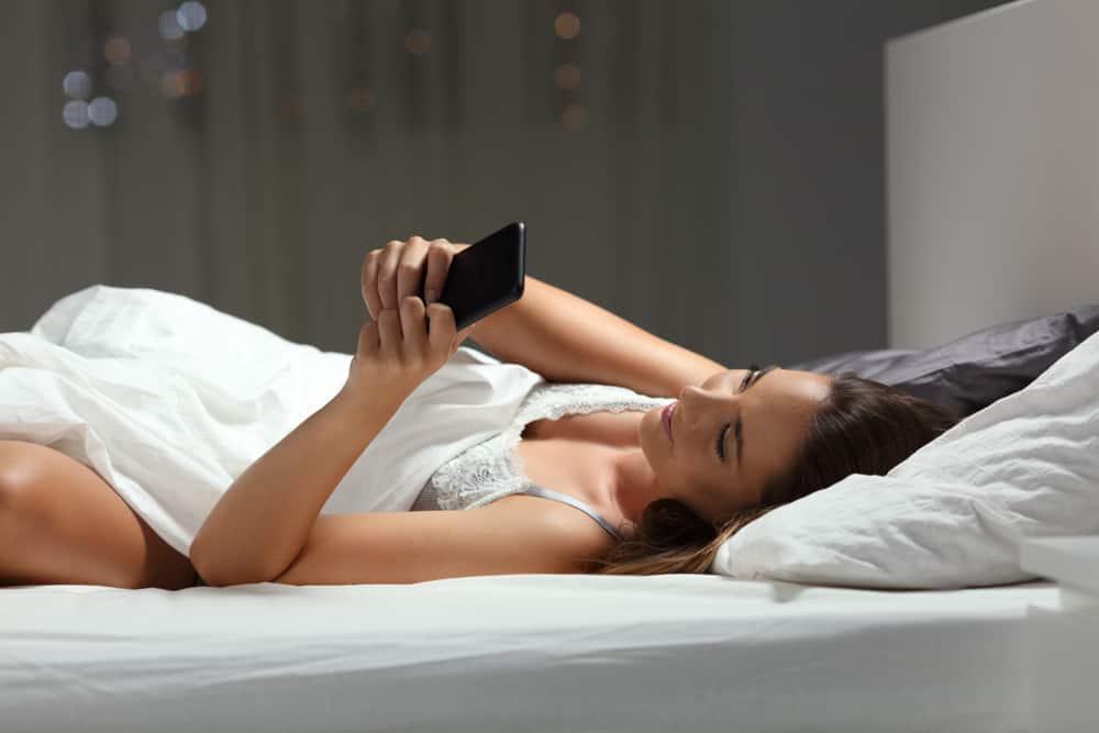 Die Frau liegt im Schlafzimmer und benutzt ein Handy