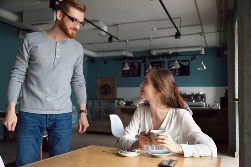 Die Frau sitzt am Küchentisch, trinkt Kaffee und schaut mit dem Mann zu
