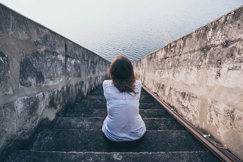 Die Frau sitzt mit dem Rücken zur Treppe