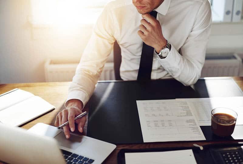 Ein Geschäftsmann mit Krawatte und weißem Hemd sitzt an seinem Schreibtisch