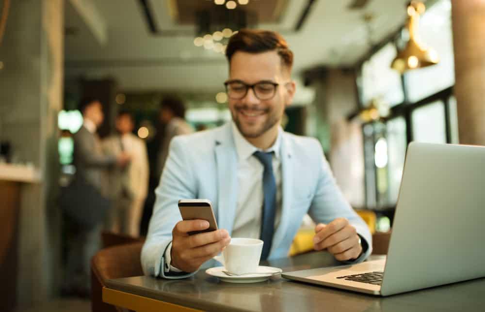 Ein Geschäftsmann sitzt und trinkt Kaffee, während er auf sein Handy schaut