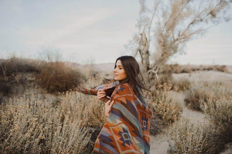 Ein Mädchen, das mit einer Decke bedeckt ist, geht durch ein Feld