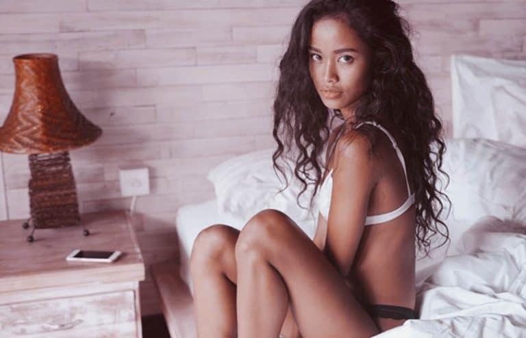 Ein Mädchen in sexy Dessous sitzt auf dem Bett
