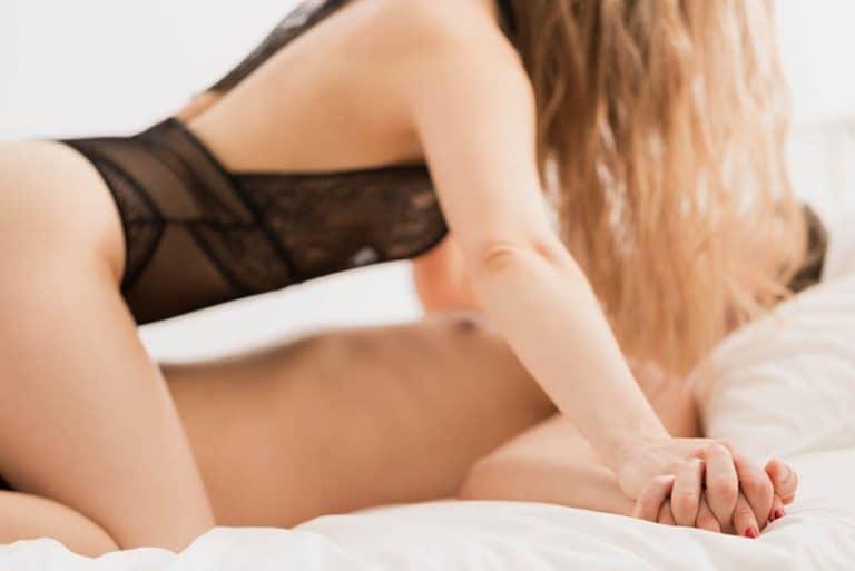 Ein Mädchen in sexy Dessous sitzt auf einem Mann