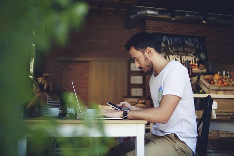 Ein Mann arbeitet an einem Laptop und hält ein Handy in den Händen